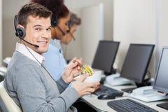 Мужской представитель обслуживания клиента имея еду Стоковое Изображение