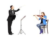 Мужской проводник оркестра сразу женская играя скрипка стоковые изображения rf