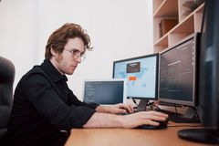 Мужской программист работая на настольном компьютере с много мониторов на офисе в программном обеспечении для того чтобы начать к стоковые изображения
