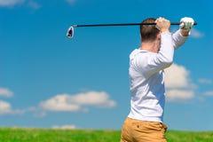 Мужской профессиональный игрок в гольф пока ударяющ шарик Стоковые Изображения RF