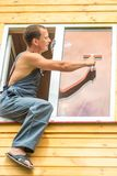 Мужской профессионал в прозодеждах очищает окно стоковое изображение