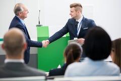 Мужской профессионал тряся руки с коллегой в лекционном зале стоковое изображение rf