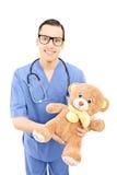 Мужской профессионал здравоохранения в форме держа плюшевый медвежонка стоковое изображение rf