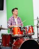 Мужской профессионал играя барабанчики в записи стоковые фото