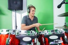 Мужской профессионал играя барабанчики в записи стоковые изображения