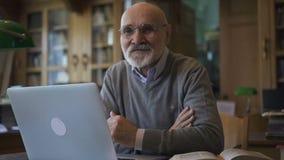 Мужской профессор биолога представляет сидеть на таблице с компьтер-книжкой в библиотеке колледжа сток-видео