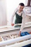 Мужской продавец в магазине рыб Стоковые Изображения