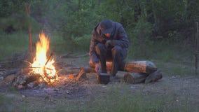 Мужской путешественник ест от огня бака близко в вечере видеоматериал