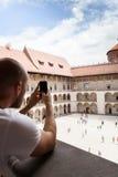 Мужской путешественник на предпосылке аркад в замке Wawel в Cracow стоковые изображения rf