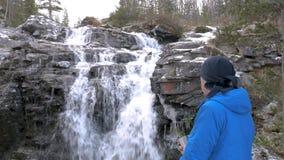 Мужской путешественник отдыхает красивым водопадом горы Конец-вверх Он выпивает чай и восхищает красивый вид акции видеоматериалы