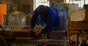 Мужской работник аранжируя прессформы в мастерской 4k видеоматериал