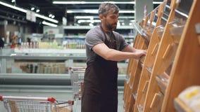 Мужской работник большого супермаркета принимает свежий хлеб от магазинной тележкаи и кладет его на полки в хлебопекарне акции видеоматериалы