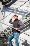 Мужской работник в защитном шлеме стоя на стальной лестнице Стоковая Фотография