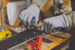 Мужской работник в мастерской обслуживания лыжи ремонтирует сползая поверхность лыж Конец-вверх руки с пластичным scrapper для re стоковая фотография rf