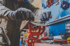 Мужской работник в мастерской обслуживания лыжи ремонтирует сползая поверхность лыж Конец-вверх руки с пластичным scrapper для re стоковые изображения