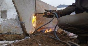 Мужской работник используя сварочный огонь в junkyard 4k акции видеоматериалы