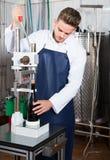 Мужской работник используя машину для того чтобы cork вино на facto игристого вина Стоковое Изображение