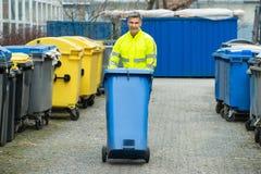 Мужской работник идя с мусорной корзиной на улице Стоковые Изображения