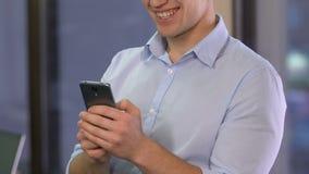 Мужской работник офиса перечисляя смартфон, проверяя данные в инструменте мобильного бизнеса акции видеоматериалы