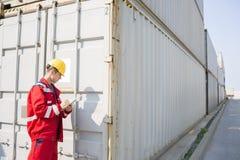 Мужской работник проверяя грузовой контейнер пока пишущ на доске сзажимом для бумаги в грузя дворе Стоковое Фото