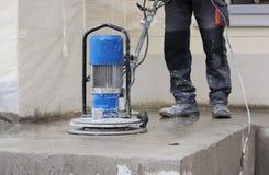 мужской работник работает при шлифовальный станок диаманта, полируя крылечко перед офисным зданием пол цемента и co Стоковое Изображение