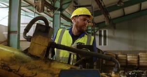 Мужской работник работая на машине в складе 4k видеоматериал