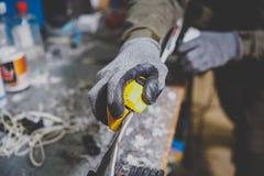 Мужской работник ремонтируя камень, край точить в мастерской обслуживания лыжи, сползая поверхности лыж точить выпушки mo стоковые изображения