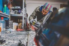 Мужской работник ремонтируя камень, край точить в мастерской обслуживания лыжи, сползая поверхности лыж точить выпушки a стоковые изображения