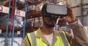 Мужской работник склада нося шлемофон VR в заливе загрузки 4k сток-видео