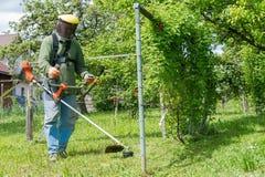 Мужской работник с триммером mo лужайки строки електричюеского инструмента Стоковые Фото