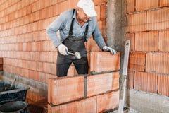 Мужской работник устанавливая кирпичи с минометом и резиновым молотком Данные о промышленности конструкции стоковые фото