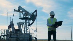 Мужской работник energetics стоит с ноутбуком рядом с деррик-краном нефти видеоматериал