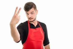 Мужской работодатель супермаркета показывая номер два стоковые изображения