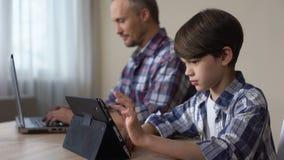 Мужской ребенк играя игру на таблетке пока отец работая на компьтер-книжке дома, устройство сток-видео