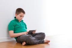 Мужской ребенк используя его таблетку пока полагающся на стене Стоковые Фотографии RF