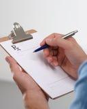 Мужской рецепт сочинительства доктора на доске сзажимом для бумаги Стоковые Изображения RF