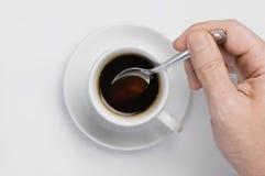 Мужской руки stir кофе медленно черный с ложкой в кофейной чашке против белой предпосылки с местом для взгляд сверху текста Стоковая Фотография RF