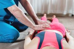 Мужской ручной висцеральный masseur терапевта обрабатывает молодого женского пациента Редактирование бедренной кости стоковые изображения rf
