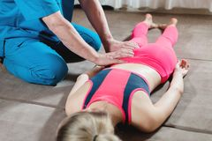 Мужской ручной висцеральный masseur терапевта обрабатывает молодого женского пациента Редактирование бедренной кости стоковое изображение rf