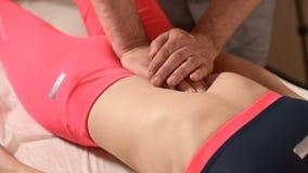 Мужской ручной висцеральный masseur терапевта обрабатывает молодого женского пациента Редактируйте внутренние органы и исключение сток-видео
