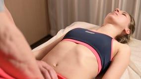 Мужской ручной висцеральный masseur терапевта обрабатывает молодого женского пациента Внешнее редактирование матки сток-видео