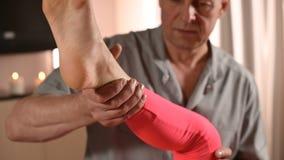 Мужской ручной висцеральный masseur терапевта обрабатывает молодого женского пациента Работа с батокс более низкой задней части и видеоматериал