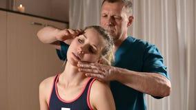 Мужской ручной висцеральный masseur терапевта обрабатывает молодого женского пациента Редактирование шеи и позвонков сток-видео