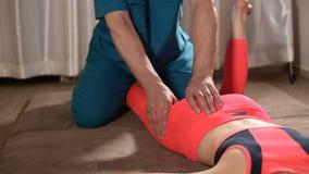 Мужской ручной висцеральный masseur терапевта обрабатывает молодого женского пациента Редактирование бедренной кости акции видеоматериалы