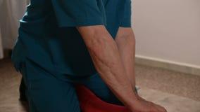 Мужской ручной висцеральный masseur терапевта обрабатывает молодого женского пациента Редактирование бедренной кости видеоматериал