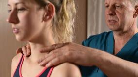 Мужской ручной висцеральный masseur терапевта обрабатывает молодого женского пациента Нагревайте плечи и шею акции видеоматериалы