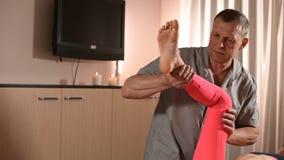 Мужской ручной висцеральный masseur терапевта обрабатывает молодого женского пациента Работа с батокс более низкой задней части и акции видеоматериалы