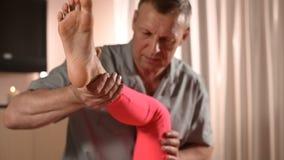 Мужской ручной висцеральный masseur терапевта обрабатывает молодого женского пациента Работа с батокс более низкой задней части и сток-видео