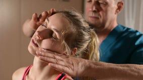 Мужской ручной висцеральный masseur терапевта обрабатывает молодого женского пациента Редактирование шеи и позвонков видеоматериал