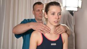 Мужской ручной висцеральный masseur терапевта обрабатывает молодого женского пациента Нагревайте плечи и шею видеоматериал